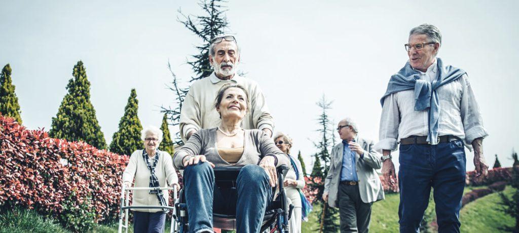 Eldercare - Man pushing woman in wheelchair